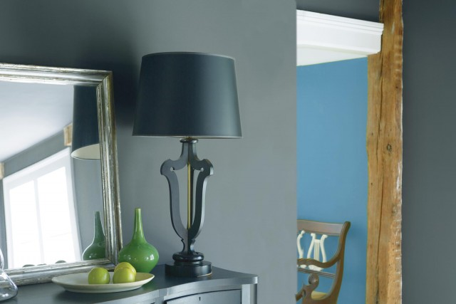 A close up of room in grey painted wall and wood pillar and black table lamps next to mirror
