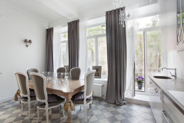 Beautiful dining room interior with long charcoal curtains from the top to bottom from the window and pattern square tiles on the floor under the family set dining table