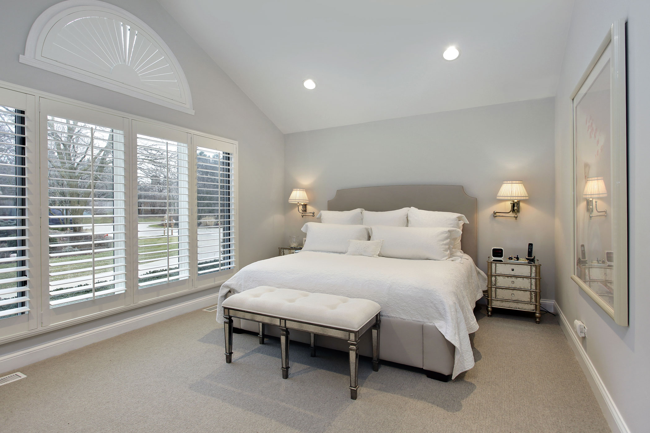 A modern bedroom interior with white wall and wooden shutters on the window with beautiful bedding with bench in the middle