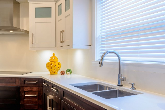 A close up modern kitchen interior with horizontal blinds and white closets on top and kitchen counter with little ornaments
